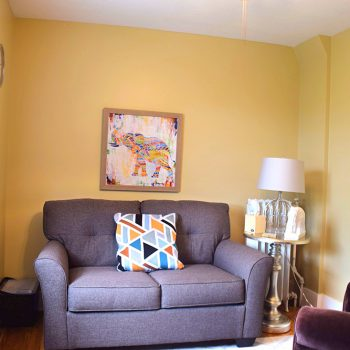 yellow room with stuffed purple loveseat and white lamp